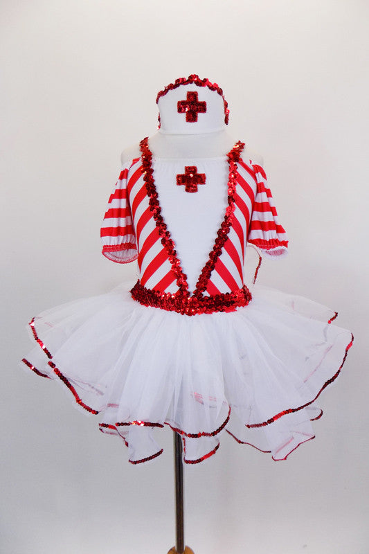 Red & white striped dress has pouf sleeves & white center edged in red sequin with large red cross applique. The attached skirt has petticoat with sequin edge. Comes with nurse hat accessory and ruffled socks. Front