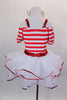 Red & white striped dress has pouf sleeves & white center edged in red sequin with large red cross applique. The attached skirt has petticoat with sequin edge. Comes with nurse hat accessory and ruffled socks. Back