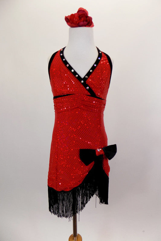 Flapper themed red sequined cross front halter dress has black crystaled piping. Skirt cuts up at left leg with black velvet bow. Edged with black fringe. Front