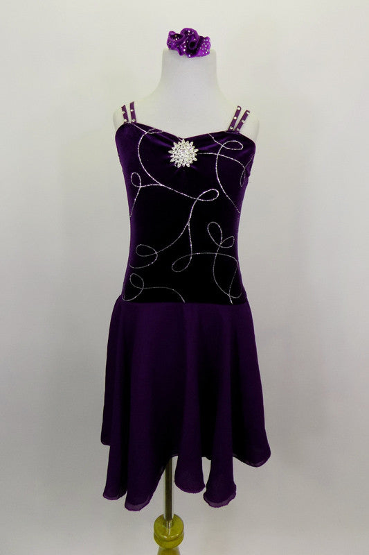 Dark purple velvet pinch front leotard dress has silver swirls on front torso with double cross straps are covered in crystals. Attached skirt is purple chiffon. Comes with hair accessory. Front