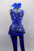 Royal blue unitard has fully sequined bodice with open back, sides & sequin peplum skirt. Has blue bow accent at the of torso & blue legging bottoms. Comes with large hair bow. Front