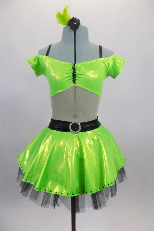 Lime green dress has nude torso with attached green bra top that has cap sleeves. Back has triple black straps joined by crystal ring. Skirt had black petticoat & crystal accents. Comes with hair accessory. Front