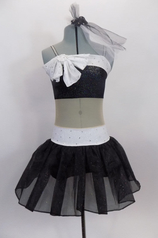 Black & white glitter dress has nude sheer center to create appearance of a 2- piece. Bust & waist have white band covered in crystals & large bow at right bust. Front