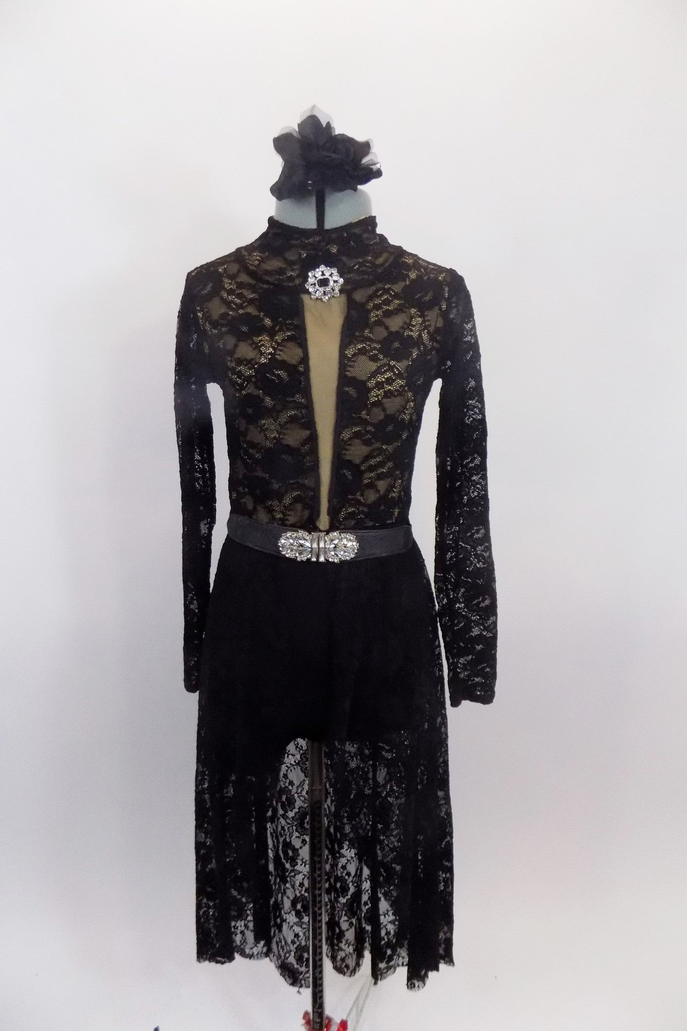 "Black lace, high neck dress has nude base & long sleeves. Front has nude ""V"" center. Dress has zip-up back & attached shorts. Comes with belt & crystal brooch.  Front"