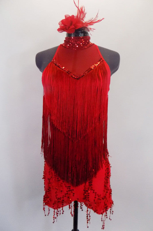 Sexy halter style, red fringed front,  short unitard has dangling sequined bottom and open back with vertical straps originating from choker neck. Sequins accent the neck and mesh bust. Comes with floral/feather hair accessory. Front