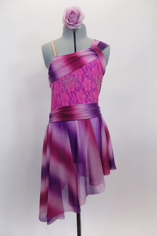 Asymmetrical dress in hues of pink and purple has striped sheer shawl accent collar that crosses at left shoulder on top of a pink lace bodice. The matching striped asymmetrical skirt has cummerbund waist. Comes with mauve rose hair accessory. Front