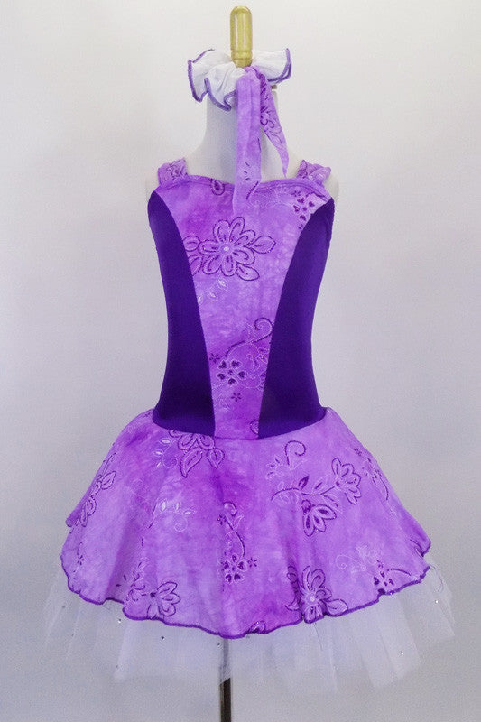 Lavender tutu dress has purple floral print skirt, front center & shoulders, with dark purple sides & back. There is a pleated white 3-layer tutu below skirt. Comes with matching hair accessory. Front