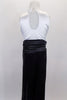 Black & white jumpsuit has white tank style upper with tuxedo shirt front, keyhole back & black bow tie accent. Black sequin pants have cummerbund waistband. Comes with black sequined hat. Back
