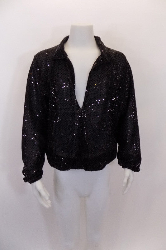 Black sequined shirt has long bishop sleeves and a deep open plunge front. The waist and wrists are elasticized for better hold. Front