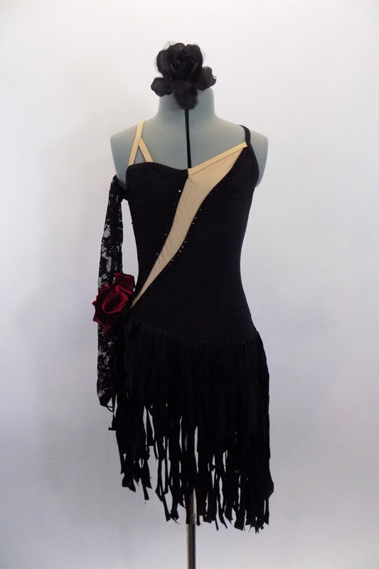 Black dress has wide fringy skirt bottom & angled, nude mesh insert. The dress has a low open back with cross straps, lace gauntlet & velvet rose at left hip. Front