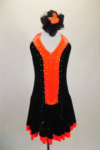 Black & bright orange halter dress has crystal covered orange front center & skirt ruffle. The back is open & ties at both center & neck. Comes with hair accessory. Front