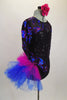 Black sequined leotard with sweetheart neckline has sheer black mesh upper with long sleeves covered in blue & magenta sequined swirls & large right hip pouf. Comes with matching floral hair accessory. Right side