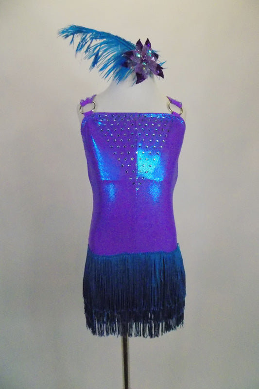 Iridescent purple-blue leotard has layered teal fringe skirt. Bodice is covered in crystals as are the triple shoulder straps. Comes with feather hair accessory. Front