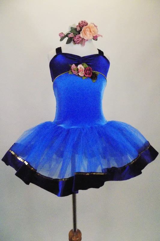 Blue tutu has deep blue velvet bodice with gold trim & cross straps. The tulle skirt has blue velvet trim accent. Front has rose detail & matching hair piece. Front