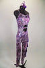 Iridescent purple animal print camisole unitard has chiffon ruffles down the left leg. Stomach area is open with crystalled band. Comes with hair accessory. Right side