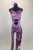 Iridescent purple animal print camisole unitard has chiffon ruffles down the left leg. Stomach area is open with crystalled band. Comes with hair accessory. Front
