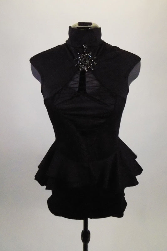 Black short unitard has layered peplum skirt, high neck & open bust. Front has center cut-out & corset lacing that reveals an attached black. Has Brooch accent. Front