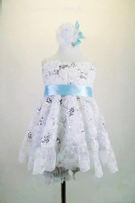 White sequined rose lace baby-doll dress has wide lace ruffle edge & wide satin baby blue sash. The back has lace-up closure. Comes with lace edged bloomers. Front