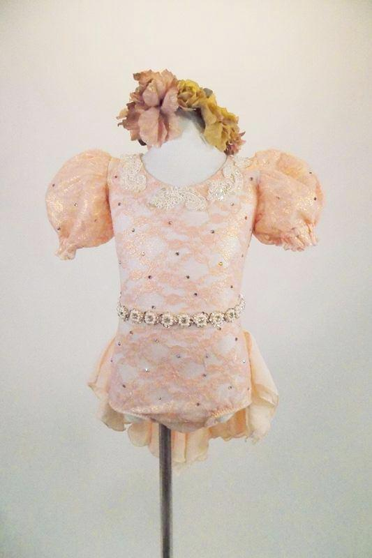 Leotard with blush lace & golden undertones has open back, large lace pouf sleeves & bridal applique The chiffon bustle & pearled belt finish the look. Comes with antiqued rose hair band. Front