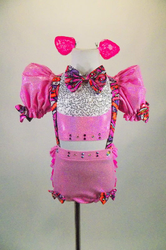 Pink piggy-themed 2-piece costume has pouf sleeved half top with keyhole back & laced back. Matching short has back ruffles, curly tail & attached suspenders.  Comes with clip-on ears. Front