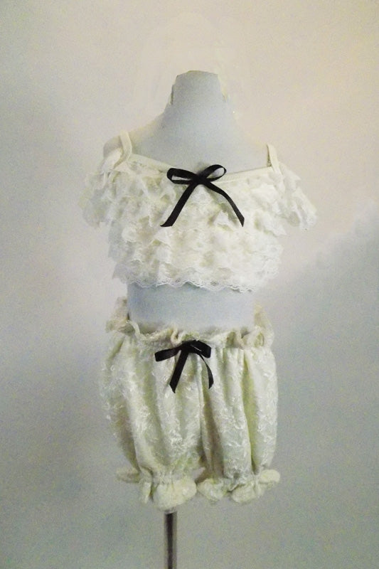2-piece ivory lace costume resembles vintage undergarments. Bottom is pouffy bloomers & bra top has lace ruffled, front, corset  lace-up back & drop shoulders. Comes with large hair accessory. Front