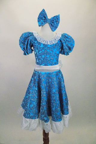 Blue brocade motif glitter velvet 2-piece costume has pouf sleeved leotard with lace collar. The matching knee-length skirt has lace trim & waistband with bow. Comes with matching hair bow. Front