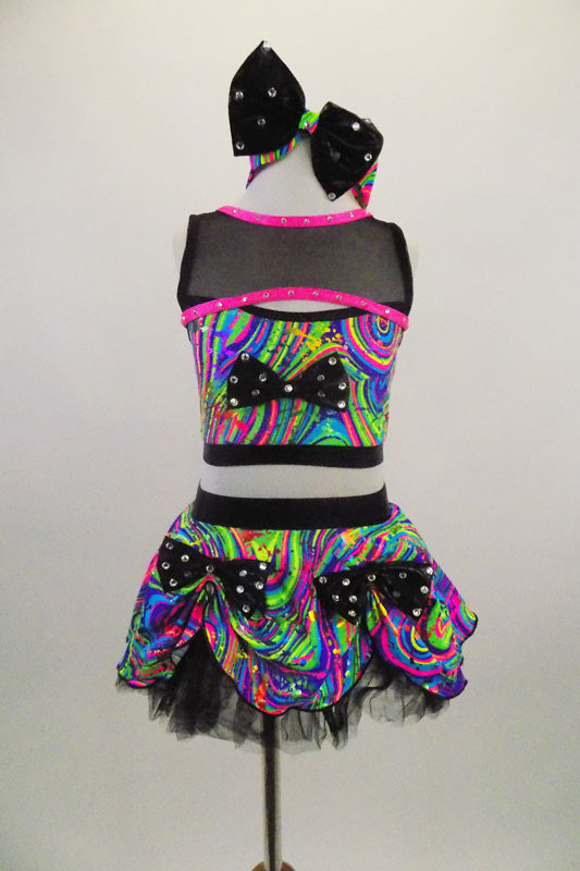 2-piece costume has bright neon swirls. The half-top has a black crystaled bow & mesh upper shrug with pink trim. Skirt has crystaled bows & tulle crinoline. Comes with matching headband. Front