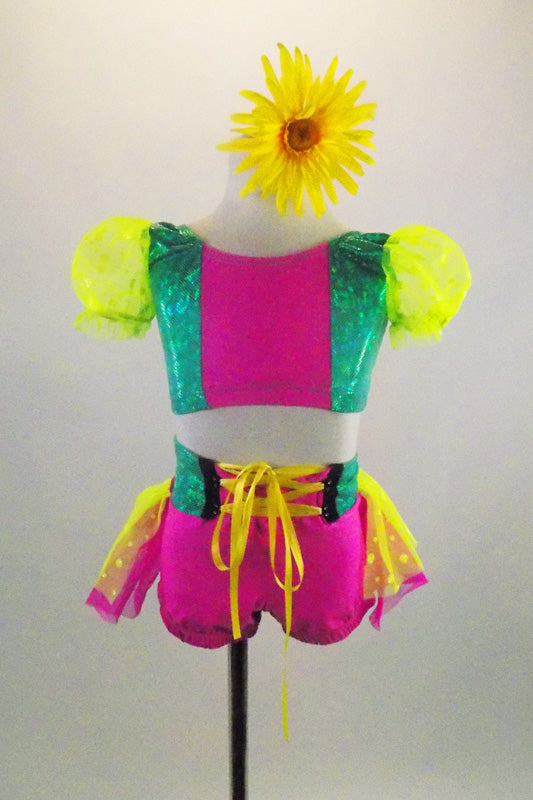 2-piece pink & green costume has bright yellow polka dot layered back bustle & pouf sleeves. Waistband has bright yellow lace up ribbon. Has daisy hair clip. Front
