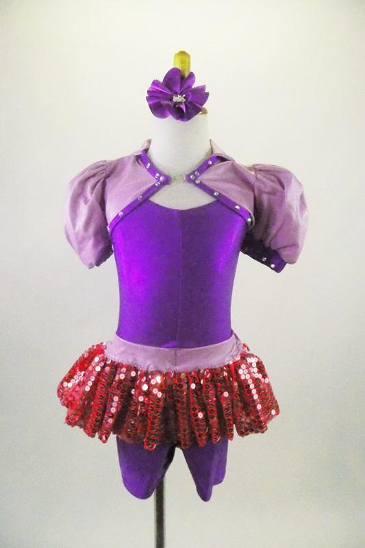 Purple short leotard has attached pink sequined short skirt with lavender waistband. The accompanying lavender shrug has pouf sleeves & crystaled purple piping. Comes with purple hair accessory. Front