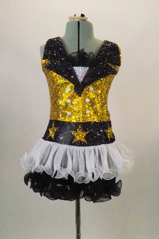 Sequined dress has gold base with black sequined lapel collar and star accent waist. The dress has sequined star covered waist & curly edge black & white skirt. Front