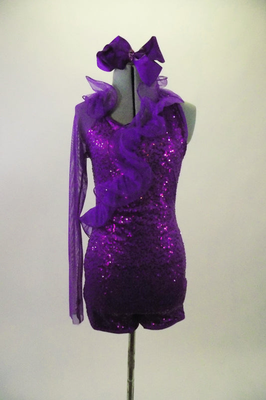Purple sequined lace short unitard has a halter neck & curly ruffled organza cascading down the front. Right sleeve is full length purple stretch mesh. Comes with matching hair accessory. Front