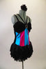 Black velvet leotard has layered sequined skirt. Bust has double straps lined with crystals & large crystal brooch. Has pink & turquoise vertical striped torso. Comes with floral hair accessory. Side