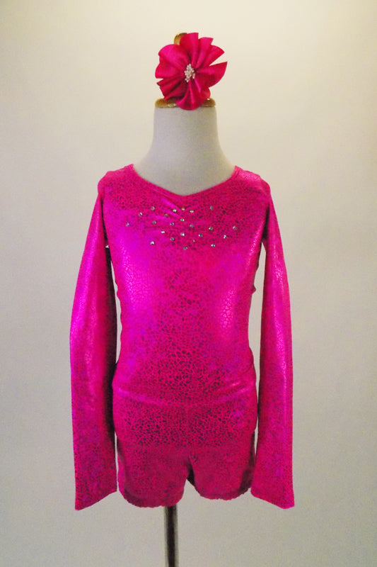 Long sleeved hot pink metallic marbled short unitard has crystalled front and back accents. The open back has a fully crystalled bow that rests at the base of the lower back. Comes with a hair accessory. Front