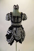 Black and white striped saloon girl themed dress has a laced bib bust area and short pouffe sleeves. The right hip is gathered with pick-ups in layers of black and black/white checkers. The back of the dress has lace-up detail. Comes with matching hair accessory. Front