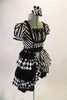 Black and white striped saloon girl themed dress has a laced bib bust area and short pouffe sleeves. The right hip is gathered with pick-ups in layers of black and black/white checkers. The back of the dress has lace-up detail. Comes with matching hair accessory. Right side