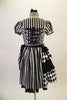 Black and white striped saloon girl themed dress has a laced bib bust area and short pouffe sleeves. The right hip is gathered with pick-ups in layers of black and black/white checkers. The back of the dress has lace-up detail. Comes with matching hair accessory. Back