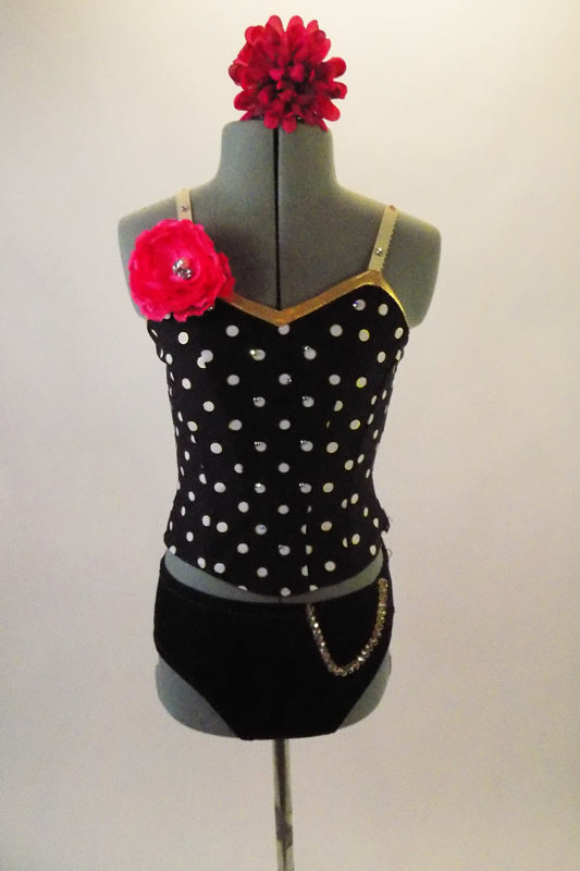 Two-costume has black and white polka dot camisole top with gold piping and jewelled flower accent at right shoulder. The matching black briefs have a chain accent at the left hip. Comes with matching hair accessory. Front