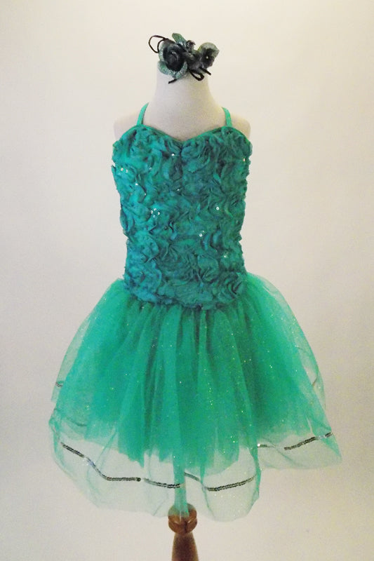 Delicate turquoise-sea green dress has chiffon ribbon rose lace front with a plain back and criss-cross straps.  The full crystal tulle skirt in shades of blue-green has silver sequin edge. Comes with crystal barrette hair accessory. Front