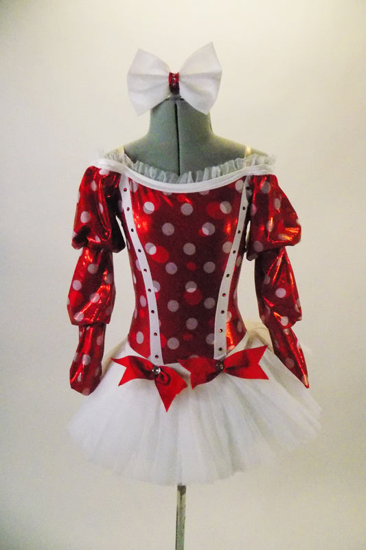 Red and white costume has red shiny bodice, large white polka dots & princess cut crystalled piping. The triple pouffed Bishop sleeves accent the off-shoulder cut with white ruffling. The finely pleated white tutu skirt has red bow accents. Front