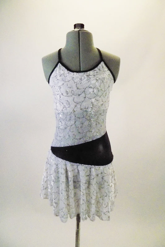 White knee-length dress has silver swirl pattern and black piping with back cross straps. The black waistband starts at the right hip and widens as it wraps around the back and front joining at the left side. Comes with a hair accessory. Front