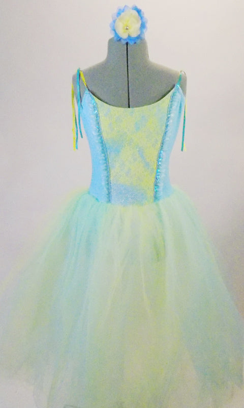 Romantic tutu dress has a pale blue bodice with blue and yellow lace front panel accented with sequined ruffle. The full tulle skirt has layers of pale blue, green and yellow for a soft pleasant flowy look. Comes with matching floral hair accessory. Front