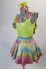 Iridescent dress has pale green bodice with rainbow coloured ruffles around the neckline and matching skirt. The neon green petticoat gives the skirt a nice fullness.  Comes with matching ruffled armband floral hair accessory. Left side