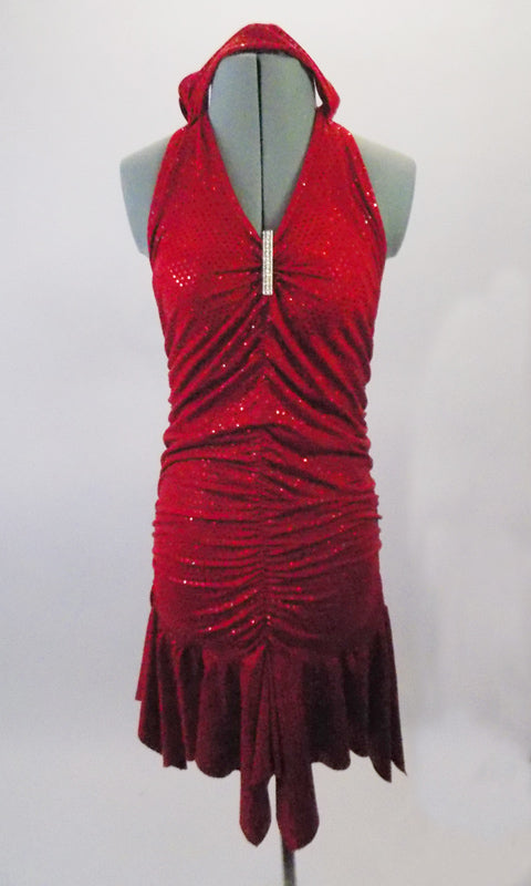 Red sparkle stretch halter neck, open-backed dress, is gathered along the front and back vertically to create a shapely silhouette. The skirt falls below the gathers for a feminine look.  A long crystal brooch highlights the gathered bust area.  Comes with matching floral headband accessory. Front
