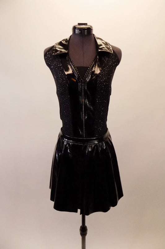 Black sequined halter leotard has black patent leatherette collar, accents and rhinestone zip front. The matching leatherette skirt has plaid lining the inner pleats. A black leatherette Brixton Brood cap completes the rebel look. Front