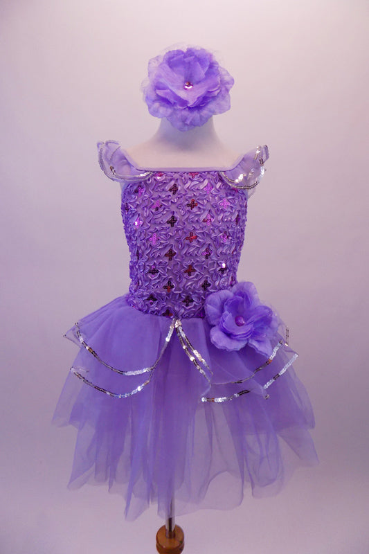 Lavender ballet dress has a rose ribbon bodice with floral sequin accents. The soft tulle layered skirt is accented with silver sequin-edged double peplum and a matching shoulder ruffle. A large lavender peony flower graces the left hip. Comes with matching peony floral hair accessory. Front
