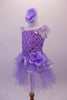 Lavender ballet dress has a rose ribbon bodice with floral sequin accents. The soft tulle layered skirt is accented with silver sequin-edged double peplum and a matching shoulder ruffle. A large lavender peony flower graces the left hip. Comes with matching peony floral hair accessory. Left side