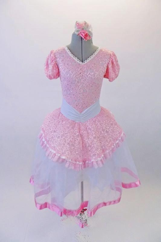 Delicate romantic tutu dress has pale pink lace bodice and overlay with pouffe sleeves, lace trim and wide gathered waistband. The long white tulle skirt has a pink satin ribbon trim.  Comes with matching floral hair accessory. Front
