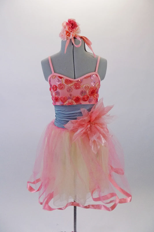 Pretty coral dance dress has coral and yellow mesh skirt with wide ribbon edging. The bodice has 3D applique flowers in shades of coral and a large coral flower accents the left side if the wide grey waistband. Comes with matching floral hair accessory. Front