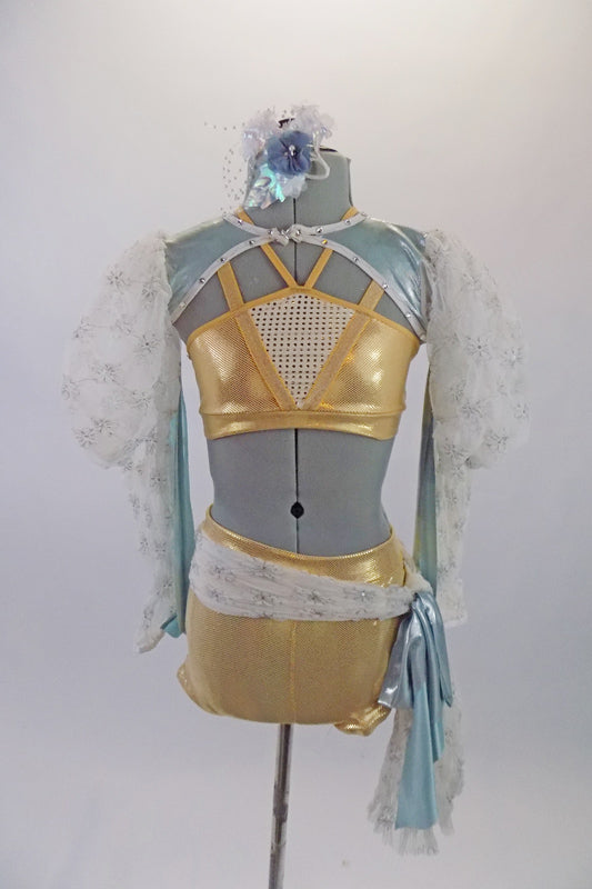 3-piece costume has a gold bra and booty short base. The bra top has a white wide mesh insert & a set of double straps of thick and thin that cross over at the back. Has a long-sleeved white lace shrug with big pouffe sleeves & looping blue bands & shoulders. Comes with hair accessory. Front