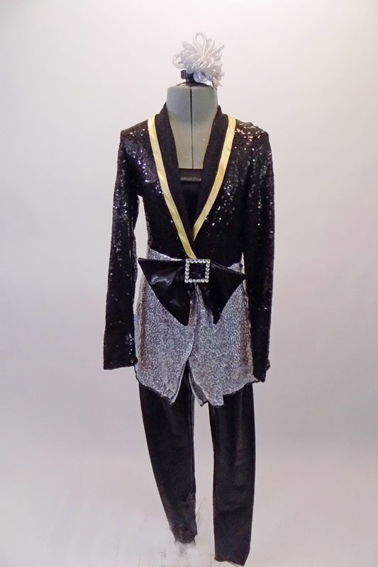 Classy three-piece costume includes a pair of black shiny leggings and matching black bandeau top. The jacket is a black and silver sequined long blazer style with gold accented lapels, cross front and a large front bow accent. Comes with matching silver hair accessory. Front